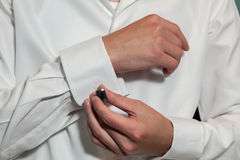 Groom putting on his cufflinks Stock Image