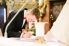 Groom putting his signature in marriage certificate. During ceremony in church. Wedding day Stock Photo