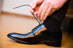 Groom putting his wedding shoes. Hands closeup Stock Photo