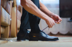 Groom putting his wedding shoes. Hands of wedding groom getting ready in suit Stock Images