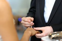 Groom putting a ring on bride's finger Royalty Free Stock Photo