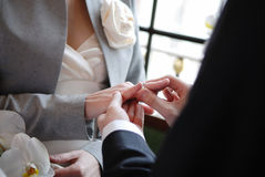 Groom putting a ring on bride's finger Stock Photos