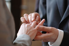 Groom putting a ring on bride's finger Stock Image