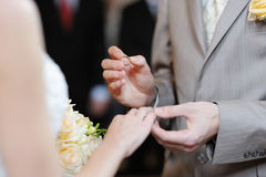 Groom putting a ring on bride's finger Stock Images