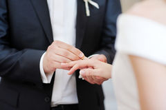 Groom putting a ring on bride's finger Royalty Free Stock Photography