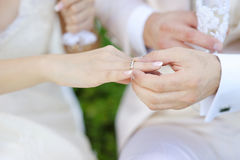 Groom putting a ring on bride's finger Royalty Free Stock Images