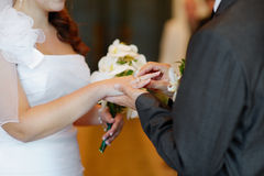 Groom putting the ring on bride's finger Royalty Free Stock Photos