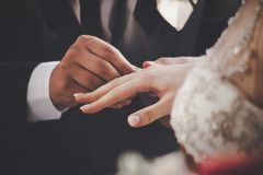 Groom Putting Ring On Bride`s Finger Royalty Free Stock Photography