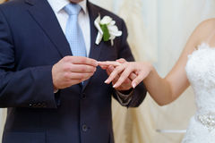 Groom is putting the ring on bride's finger Royalty Free Stock Images