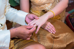 Groom putting a ring on bride s finger Stock Photo
