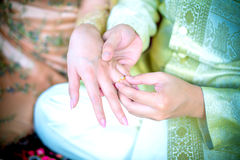 Groom putting a ring on bride's finger Stock Photography