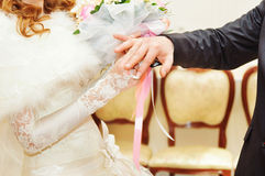 Groom putting ring on bride Royalty Free Stock Images