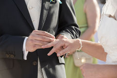 Groom putting ring on a brides finger Stock Photos