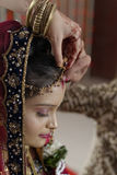Groom putting Sindoor on Bride's forehead in Indian Hindu wedding. Royalty Free Stock Photos