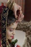 Groom putting Sindoor on Bride's forehead in Indian Hindu wedding. Royalty Free Stock Photos