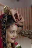 Groom putting Sindoor on Bride's forehead in Indian Hindu wedding. Stock Image