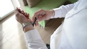 The groom putting a watch and prepare to wedding. Ceremony stock footage