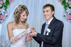 Groom putting a wedding ring on bride finger. In wedding day stock photos