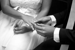 Groom putting a wedding ring on bride finger. Groom putting a wedding ring on bride`s finger in black and white stock image