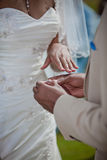 Groom putting a wedding ring on bride's finger Royalty Free Stock Photography