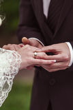 Groom putting a wedding ring. On bride's finger Stock Photos