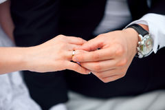 Groom putting wedding ring on bride's finger.  Royalty Free Stock Photography