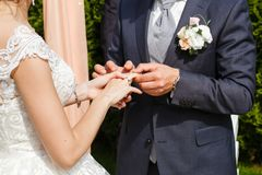 Groom putting a wedding ring on bride`s finger. Outdoor royalty free stock image