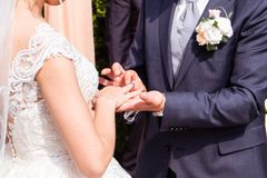 Groom putting a wedding ring on bride`s finger. Outdoor stock images