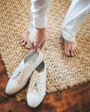 Groom putting on white shoes for the beach wedding on a tropical Stock Photos