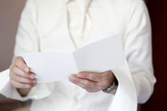 Groom is reading a white greeting card Royalty Free Stock Photos