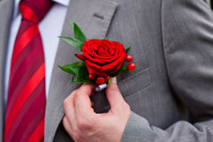 Groom in red tie with rose on his jacket Stock Photo
