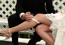 Groom removing the garter Royalty Free Stock Photos