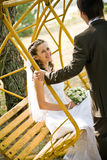Groom rocking bride on swing Stock Image