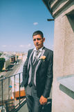 Groom on the roof of the city in a suit. With a plastron and buttonhole Stock Images