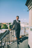 Groom on the roof of the city in a suit. With a plastron and buttonhole Royalty Free Stock Photo