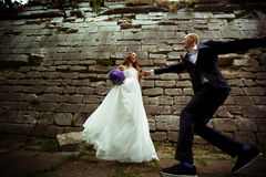 Groom runs to a bride while she waits for him behind a stone wal Stock Photo