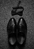 Groom`s accesories close up black and white. Close up image of shoes and bow tie of groom on dark background Royalty Free Stock Photography