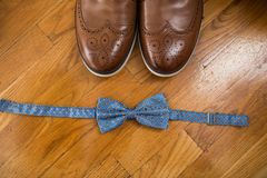 The groom`s accessories. Blue bow tie and a part of brown leather shoes on a wooden background. Accessories Royalty Free Stock Image
