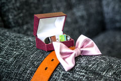 The groom`s accessories, pink bow tie, belt, cuff links. The groom`s sophisticated accessories including cuff links in the box, leather brown belt and pink bow royalty free stock photography
