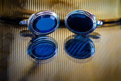 Groom`s blue buttons on shiny reflective surface. Indoor shot artificial light Royalty Free Stock Photos