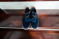 Groom`s blue suede shoes and  bow. Groom`s blue suede shoes and a blue dotted bow tie on the stairs Stock Photography