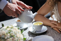 Groom's and bride's hands on the tea table Royalty Free Stock Photography