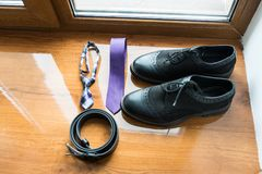 The groom`s and a dog's wedding accessories. Lilac neck tie and a black leather belt and black shoes on a wooden background. Details Royalty Free Stock Photo
