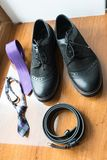 The groom`s and a dog's wedding accessories. Lilac neck tie and a black leather belt and black shoes on a wooden background. Wedding Royalty Free Stock Image