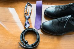 The groom`s and a dog's wedding accessories. Lilac neck tie and a black leather belt and black shoes on a wooden background. Details Royalty Free Stock Photos