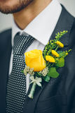 Groom's hand arranging yellow boutonniere flower on suit Stock Photography
