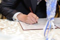 Groom's Hand with Pen Stock Photos