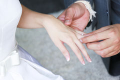 Groom's hand putting a wedding ring. On the bride's finger Royalty Free Stock Photos
