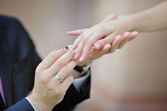 Groom's hand putting a wedding ring on the bride's finger.  royalty free stock images