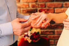 Groom`s hand putting a wedding ring on the bride`s finger. Marriage hands with rings royalty free stock photo